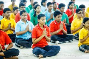 Kolkata young people meditating padmasana namaste eyes closed