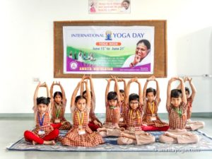 young kids doing seated arm raise pose