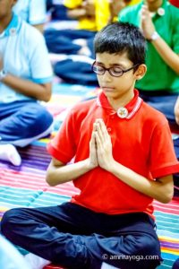 young boy meditating with namaste pose