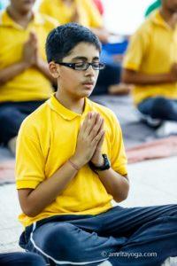 boy in yellow in meditation namaste pose