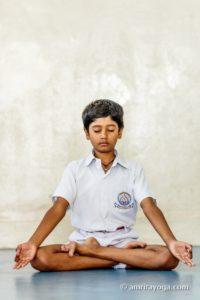 young child in white in padmasana meditation pose