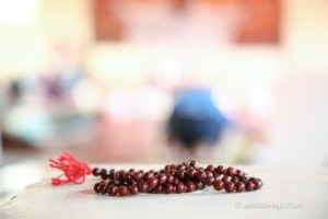 dark brown wooden mala beads with red tassel
