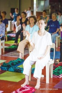 group chair seated meditation with hand raised