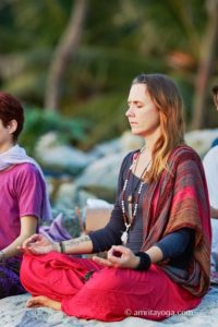 woman meditating on beach at amritapuri