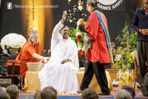 Amma showers a guest with flowers as She gets garlanded