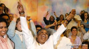 Amma Singing with arms raised