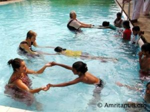 amritapuri residents teaching village children how to swim