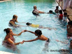 amritapuri residents teaching village children how to swim