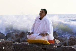 amma sitting on beach rocks ma om