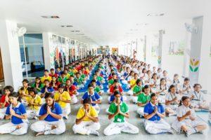 amrita yoga large hall of children in namaste