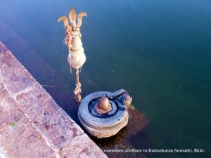 shiva linga on river ghat with trident