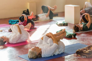 laying down holding knees yoga asana